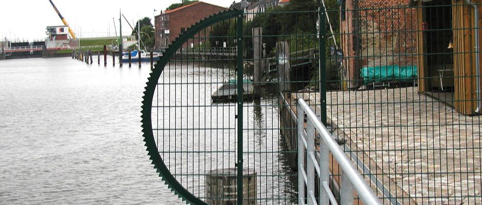 """Sicherheitszaun an einer Hafenmole mit einer sogenannten """"Sonne"""" als Abschluss am Wasser."""