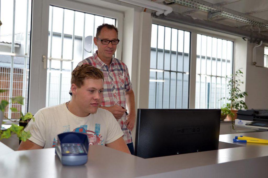 Azubi Kaufmann für Büromanagment mit Ausbilder am PC.
