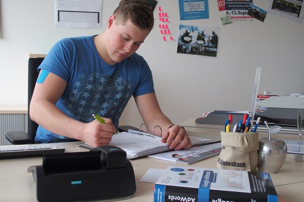 Azubi Kaufmann für Büromanagment am Schreibtisch.