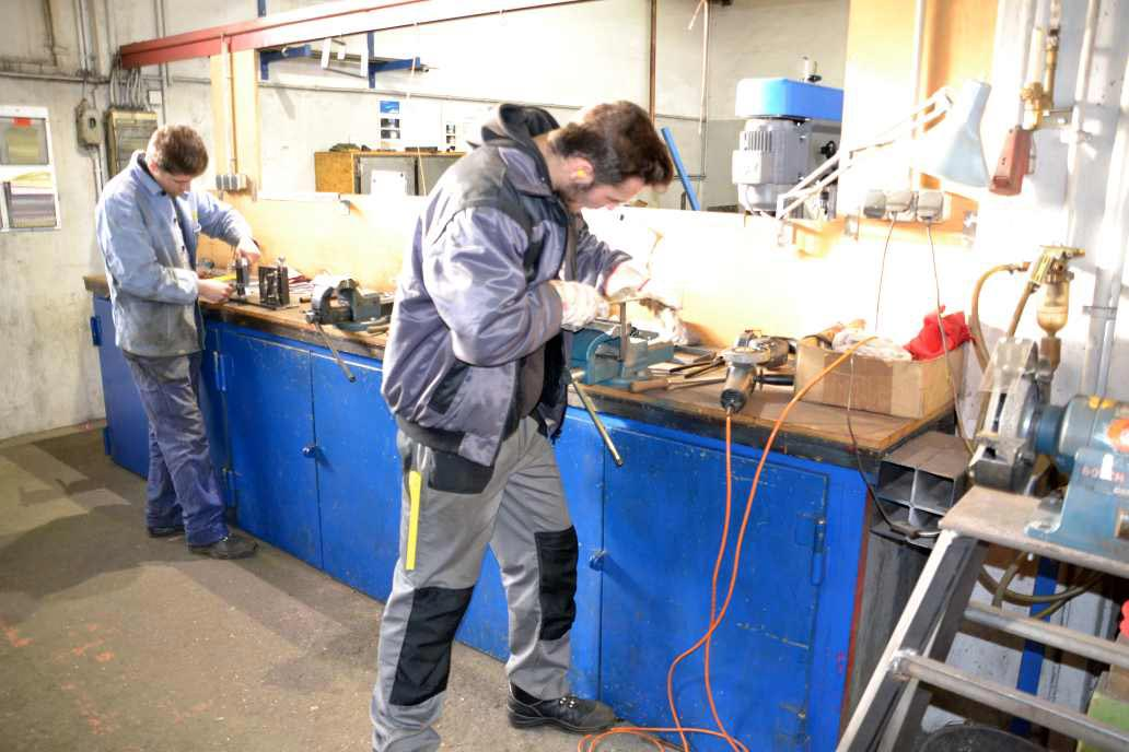 Die Ausbildung für Metallbauer*in - Fachrichtung Konstruktionstechnik findet bei Gawron im ersten Jahr in der Lehrwerkstatt statt. Hier feilt ein Auszubildender an einem Werkstück.
