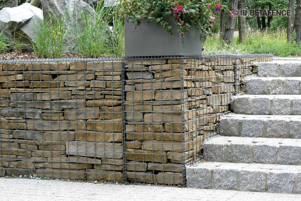 Eine Mauer aus Gabionen mit einer Füllung aus geschichteten Steinen.