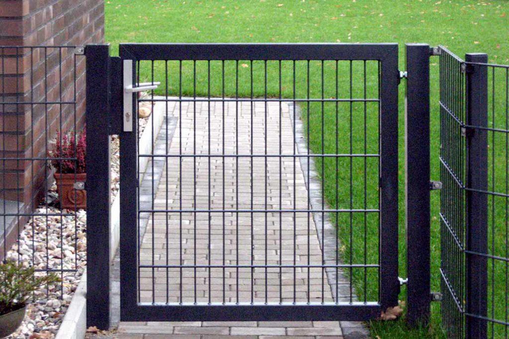 Eine Stahlmattentür im Zaun als Zugang zum Grundstück.