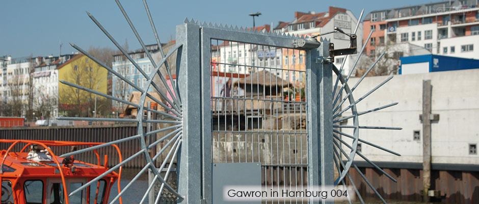 """Stahlmattentür mit einer seitlichen """"Sonne"""" als Übersteigschutz auf einem Ponton mit Blick zur Hamburger Hafenstraße."""