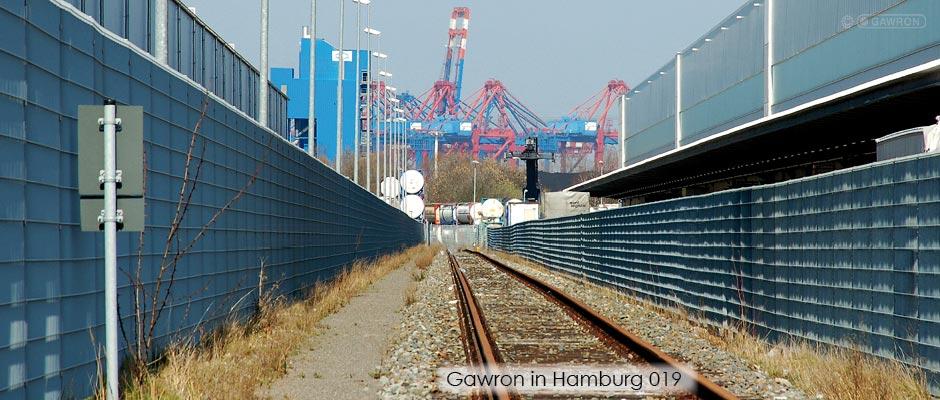 Stahlmattenzaun links und rechts an Gleisanlagen im Hamburger Hafen.