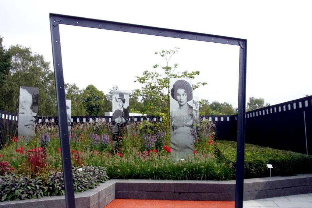 Blick durch einen Stahlrahmen auf ein Beet mit Fotos berühmter Schauspieler*innen auf der Landesgartenschau in Norderstedt.