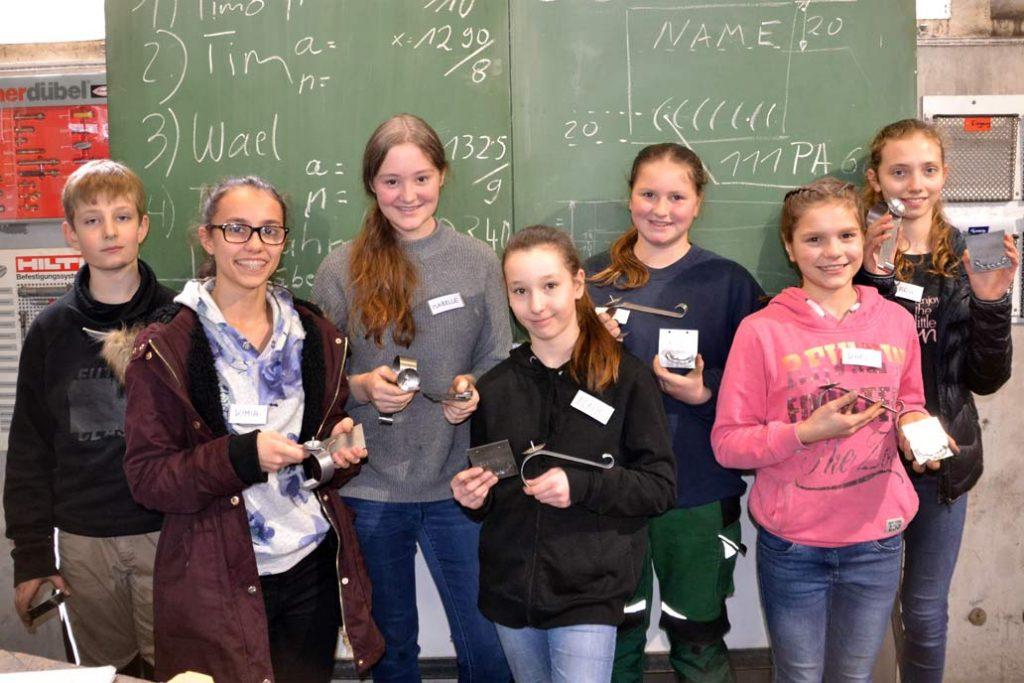 Girls'Day 2019: sechs Mädchen und ein Junge in unserer Lehrwerkstatt mit ihren selber gefertigten Objekten aus Metall.