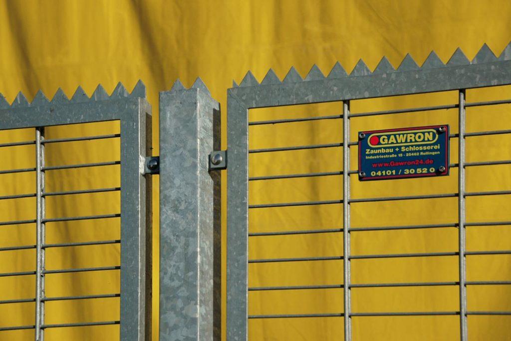 ̵Detail eines Pfostens vom Sicherheitszaun an der Messe Hamburg. Der Doppelstabmattenzaun und die Pfosten haben als oberen Abschluss eine Zackenleiste als Übersteigschutz