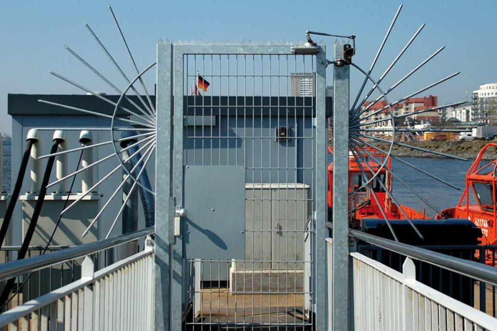 """̵Eine Stahlmattentür auf einem Ponton mit Blick auf die Hamburger Hafenstraße. Auf jeder Seite mit einer """"Tür-Sonne"""" gegen Umsteigen geschützt."""
