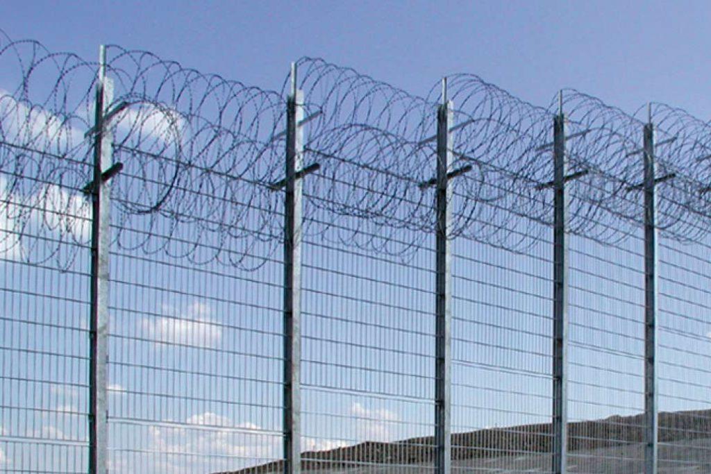 Hochsicherheitszaun mit Übersteigschutz aus mehreren Rollen Natodraht.