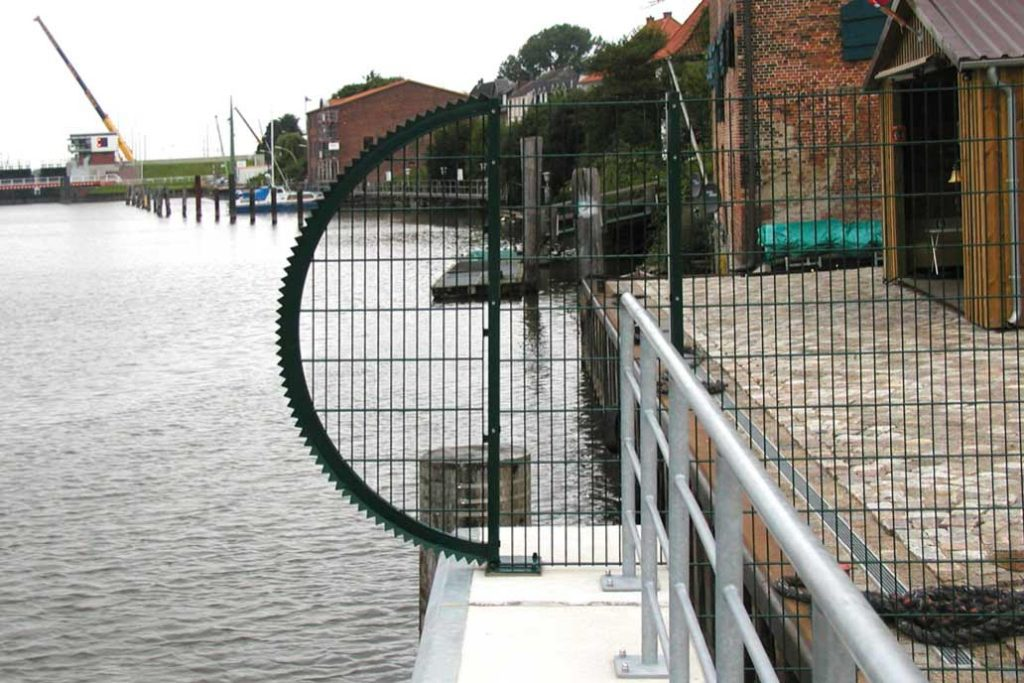 """Dieser Sicherheitszaun an einer Hafenmole hat als Abschluss auf der Wasserseite eine sogenannte """"Sonne"""" zum Schutz vor Umsteigen"""