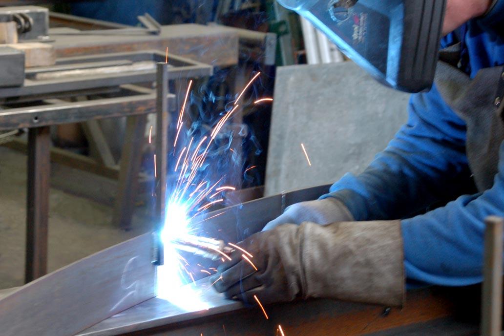 Ein Metallbauer schweißt ein Werkstück.