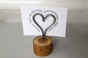 """Aus Draht gebogenes Herz auf einem Holz mit einer Karte """"Herzlichen Dank an die vielen ehrenahmtlichen Helfer*innen!"""""""