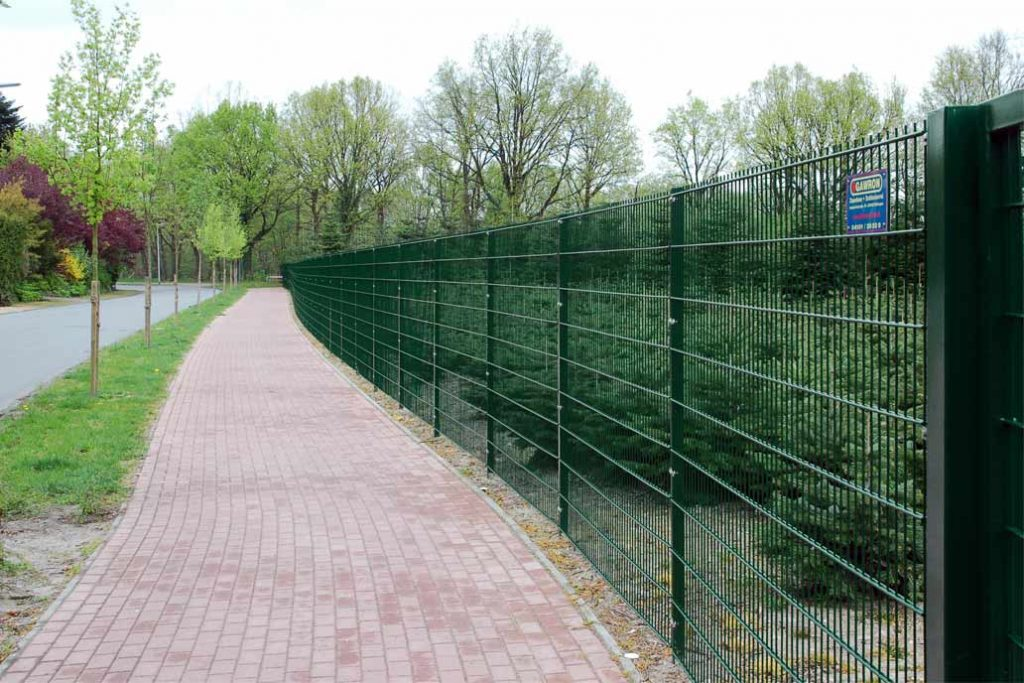 180 cm hoher grüner Stahlmattenzaun zwischen einem Fußweg und einer Baumschule.
