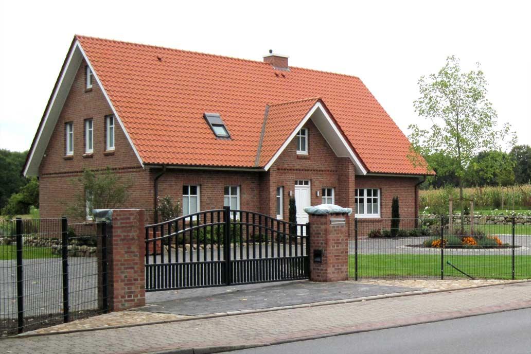 Ein geschwungenes Drehflügeltor mit Mauerpfeilern vor einem Einfamilienhaus in der Landschaft.