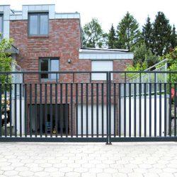 Drehflügeltor mit Stabfüllung vor einem Einfamilienhaus