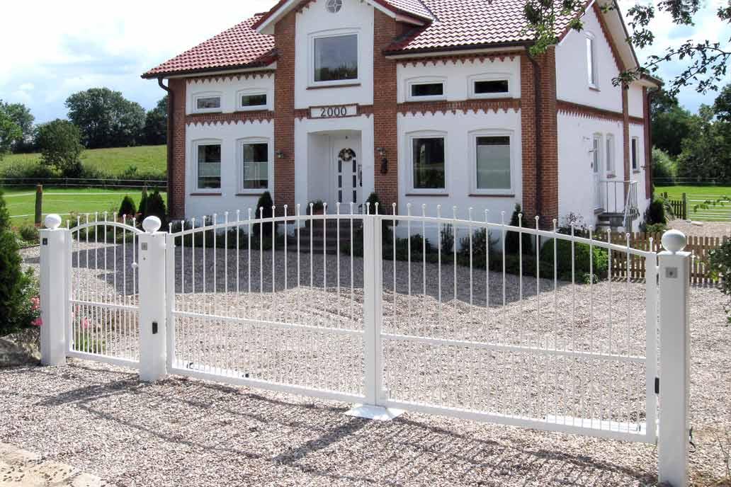 Drehflügeltor und Tür in weiß mit leichter Stabfüllung mit Kugeln. Im Hintergund ein Hof in der Landschaft.