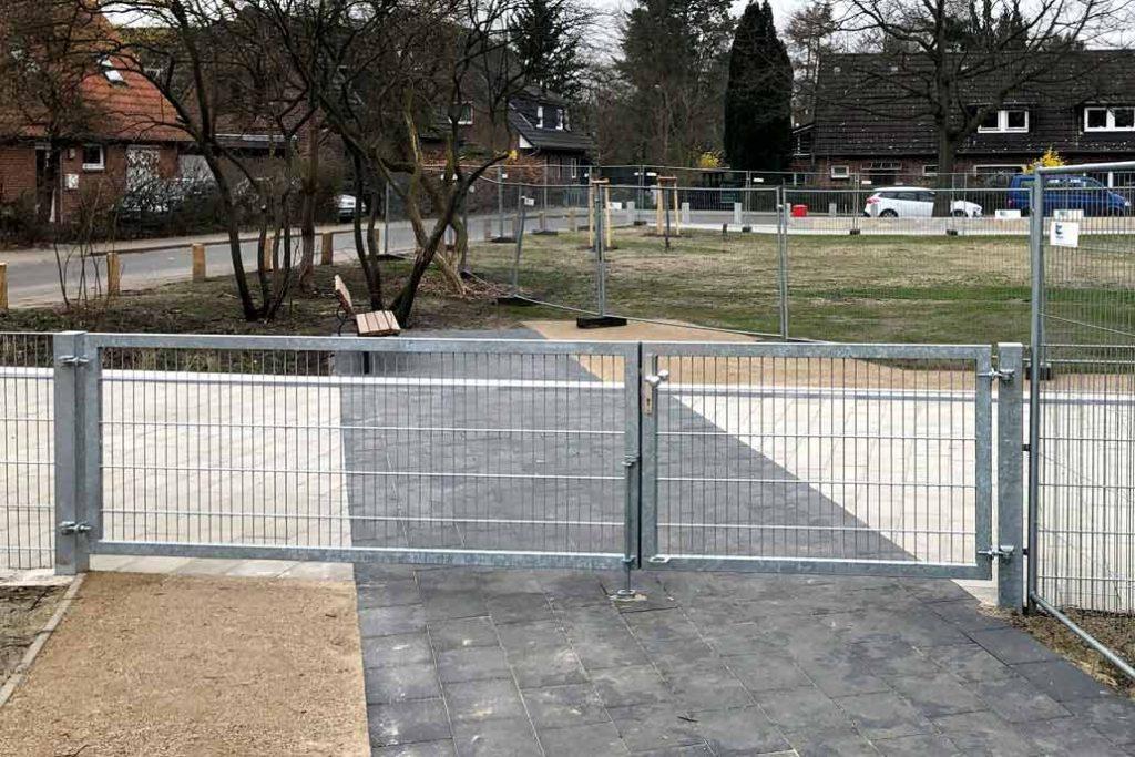 Drehflügeltor mit Stahlmattenfüllung an einem Spielplatz. Die Schenkel des Tors sind unterschiedlich breit. Der kleinere Flügel kann als Tür verwendet werden.