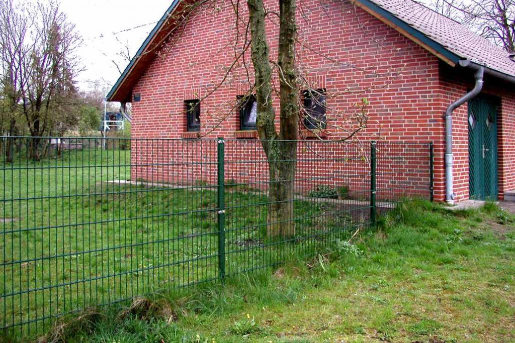 120 cm hoher grüner Stahlmattenzaun mit T-Pfosten vor einem Rotklinkerhaus mit Rasen und großem Kastanienbaum.