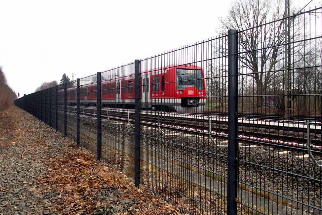 Stahlmattenzaun an der Bundesbahnstrecke in Halstenbek mit roter S-Bahn im Hintergrund.