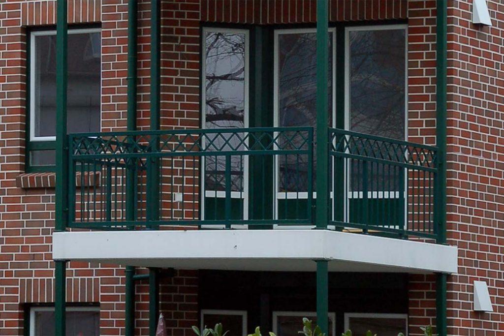 Vorstellbalkon mit grünem Stahlgeländer. Das Geländer hat Rauten als Zierelement.
