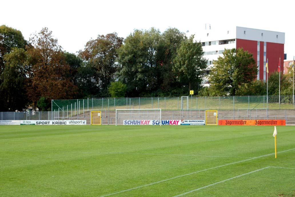 Sportplatz mit Ballfang und Lehngitter. An dem Lehngitter ist Bannerwerbung befestigt.