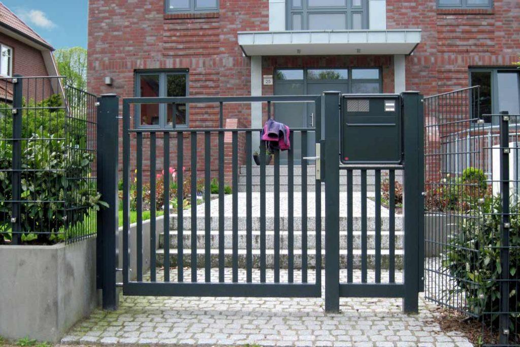 Individuelle Gartentür mit Briefkasten im Element daneben.