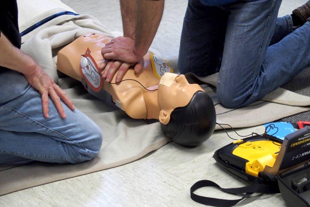 Übung an der Puppe mit dem Defibrilator bei der Erste Hilfe Ausbildung.