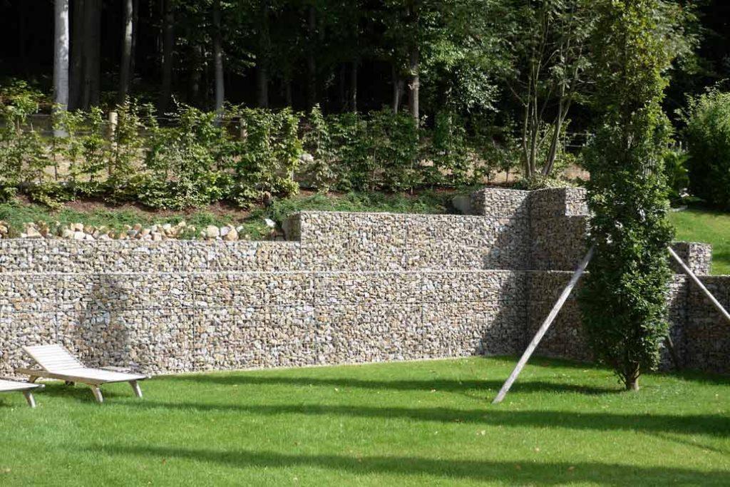 Gabionen an einem Hang als Grenze zwischen Wald und Garten.