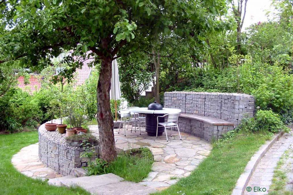 Eine Sitzecke unter einem Apfelbaum mit Mauern und Sitzbank aus Gabionen.