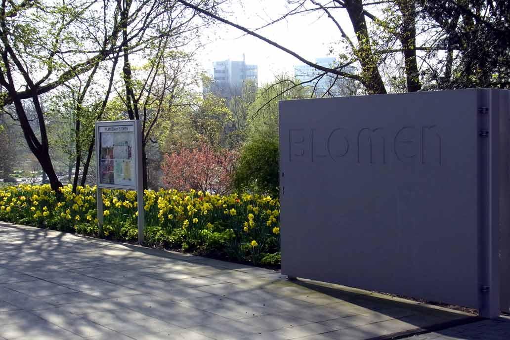 Eingang zu Planten un Blommen in Hamburg mit Blick auf den geöffneten Torflügel und ein Beet voller blühender Osterglocken