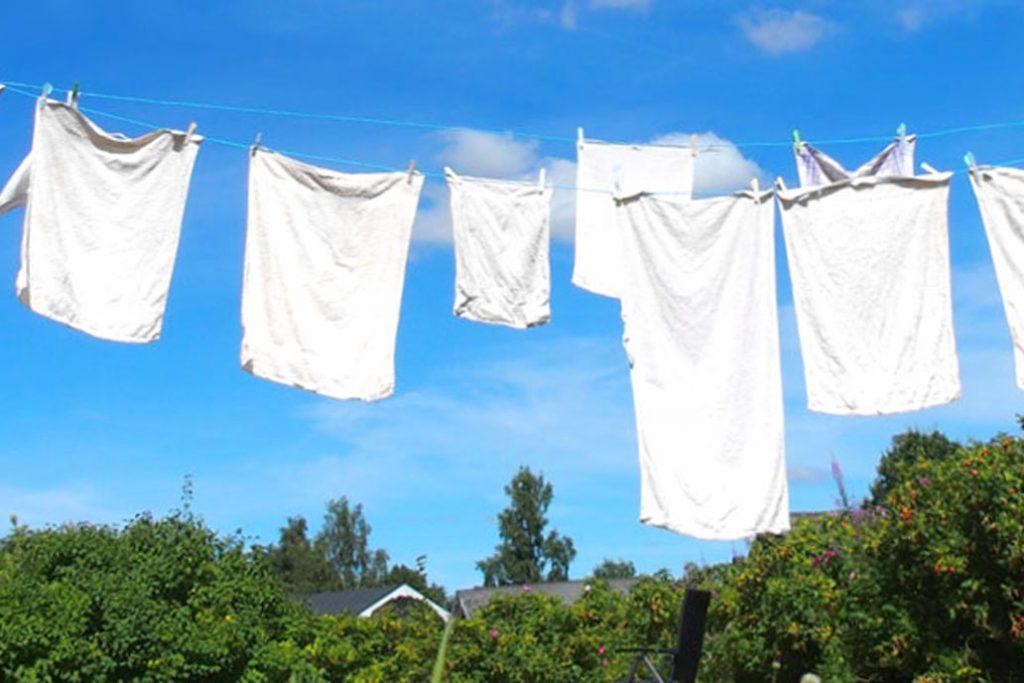 Wäsche auf der Leine zwischen Wäschepfosten vor blauem Himmel.