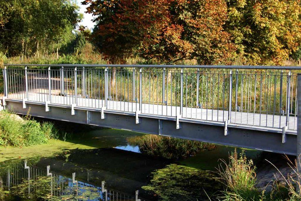 Eine Fußgängerbrücke aus Stahl über einen Fluß.