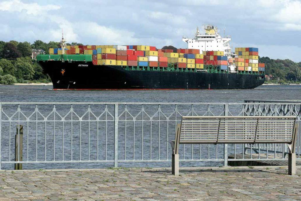 Geländer an der Elbe in Hamburg mit Blick auf ein Containerschiff.
