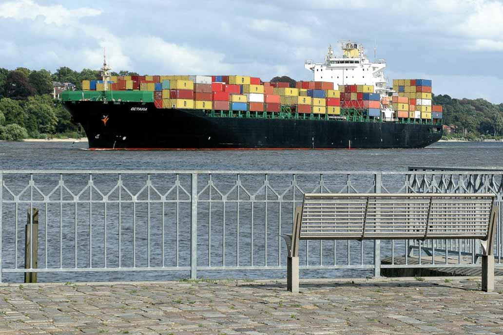 Geländer an der Elbe mit Blick auf ein Containerschiff.