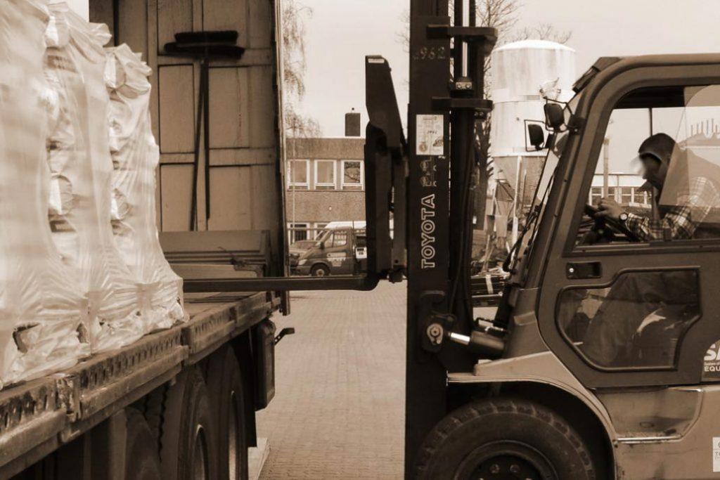 Ein Staplerfahrer entlädt einen LKW mit Zaunmaterial auf dem Hof von Gawron & Co.