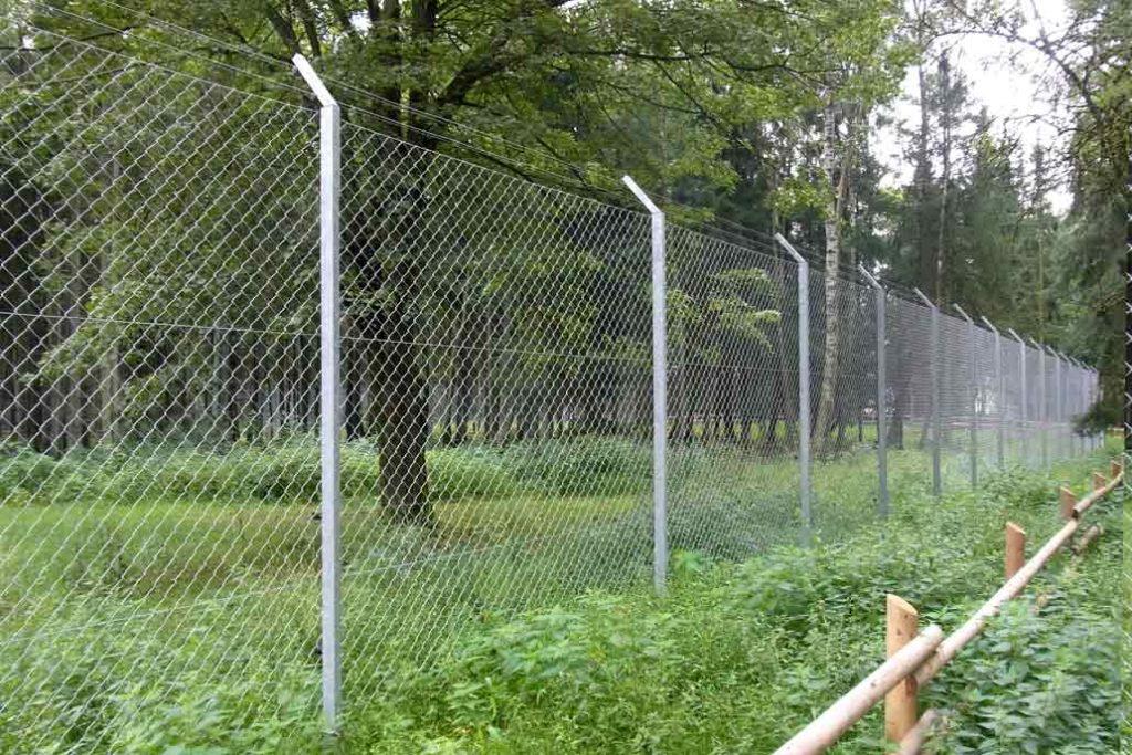 Drei Meter hoher Sicherheitszaun aus Maschendraht um das Wolfsgehege im Tierpark Eekholt. Am oberen Ende mit abgewinkelten Pfosten mit zwei Reihen Maschendraht.
