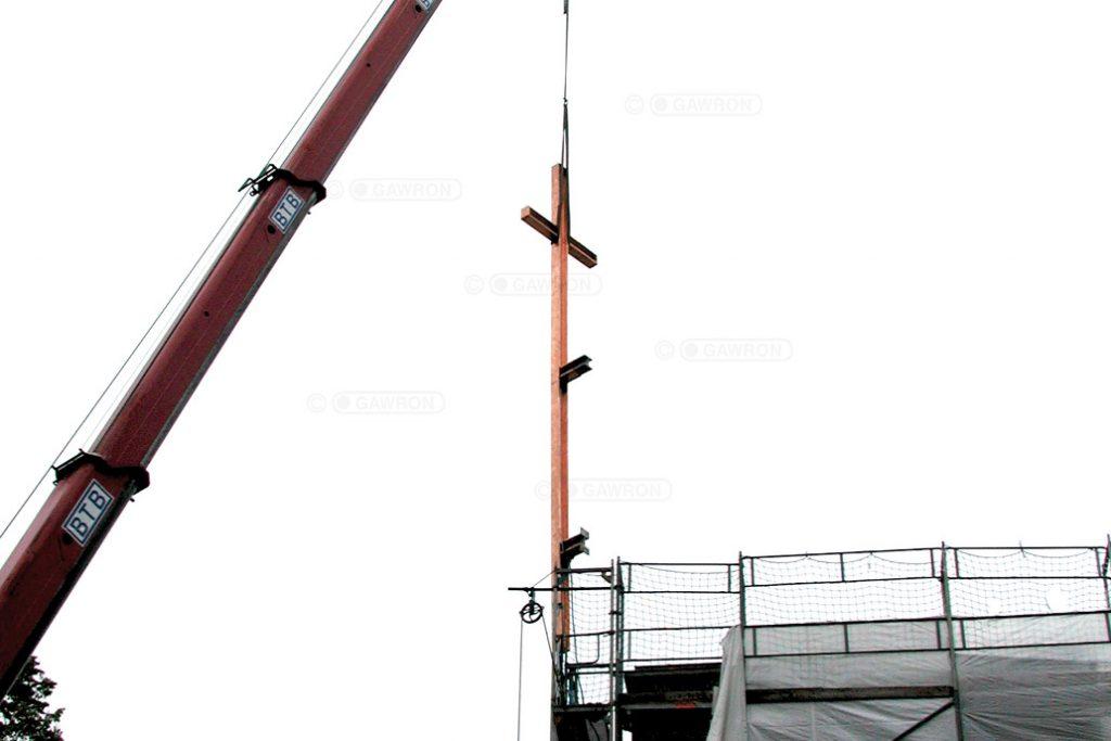 Mit Hilfe eines Krans wird das sanierte Kreuz der Maria grün Kirche in Hamburg wieder an seinem angestammten Platz montiert.