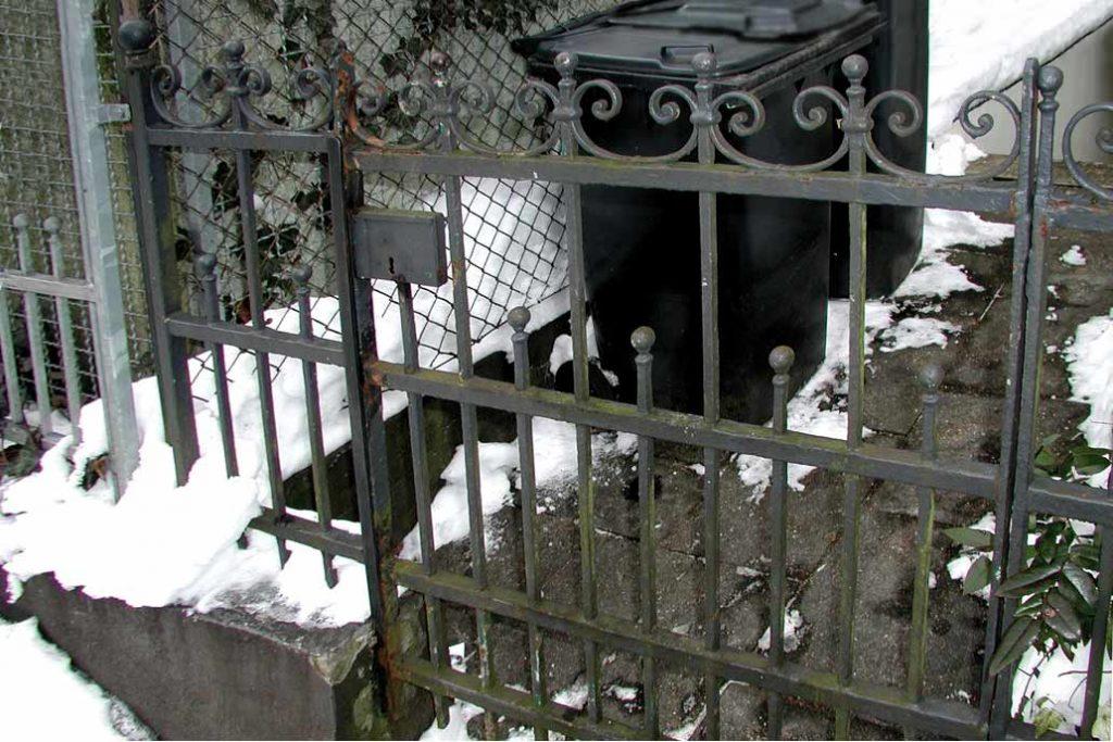 Ein histroische Ziergitter mit einer Tür vor der Sanierung. Das Metall ist stark von Rost angegriffen.