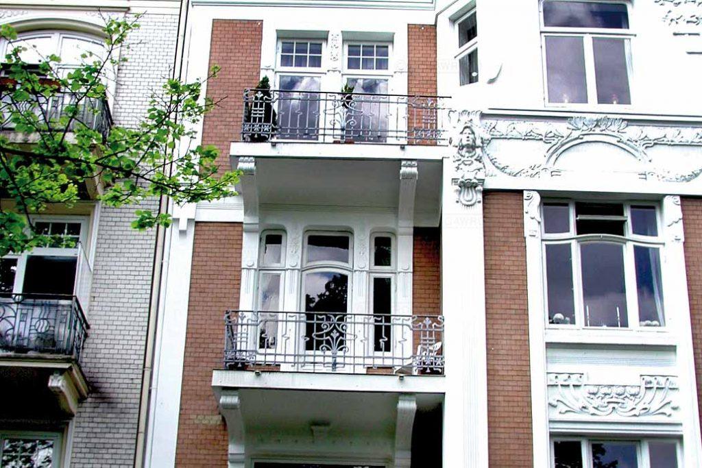 Balkone eines Gründerzeithauses mit sanierter Bodenplatte und historischem Geländer.
