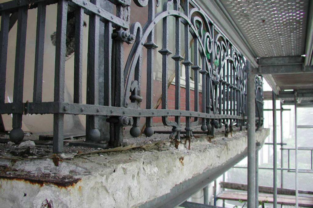 Detail einer Balkonbodenplatte und eines historischen Balkongeländers, die stark Sanierungsbedürftig ist.