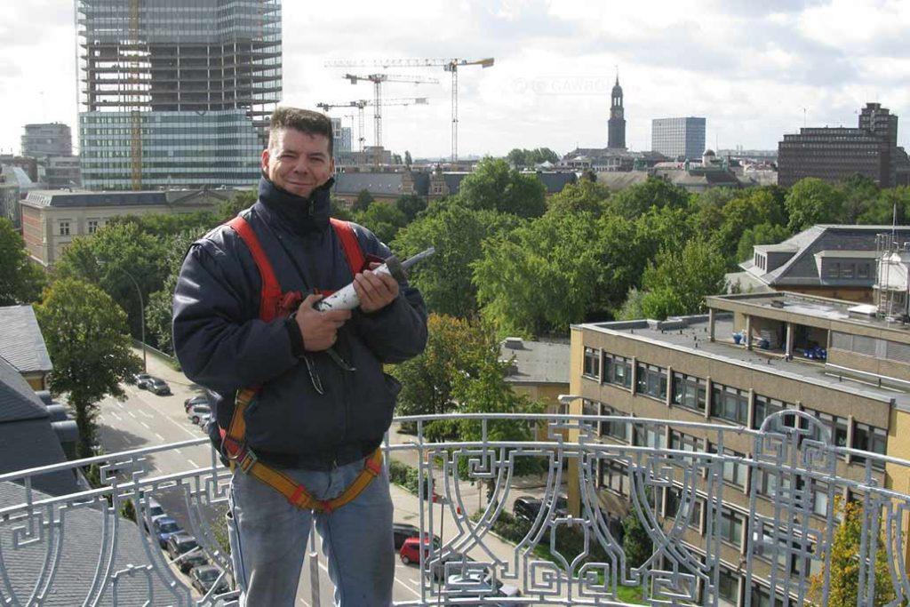 Ein Metallbauer montiert über den Dächern von Hamburg das sanierte historische Dachgeländer auf dem Bucerius Law Forum.