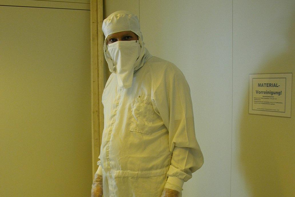 Monteur in spezial Schutzkleidung bei der partikelarmen Arbeit in Reinräumen