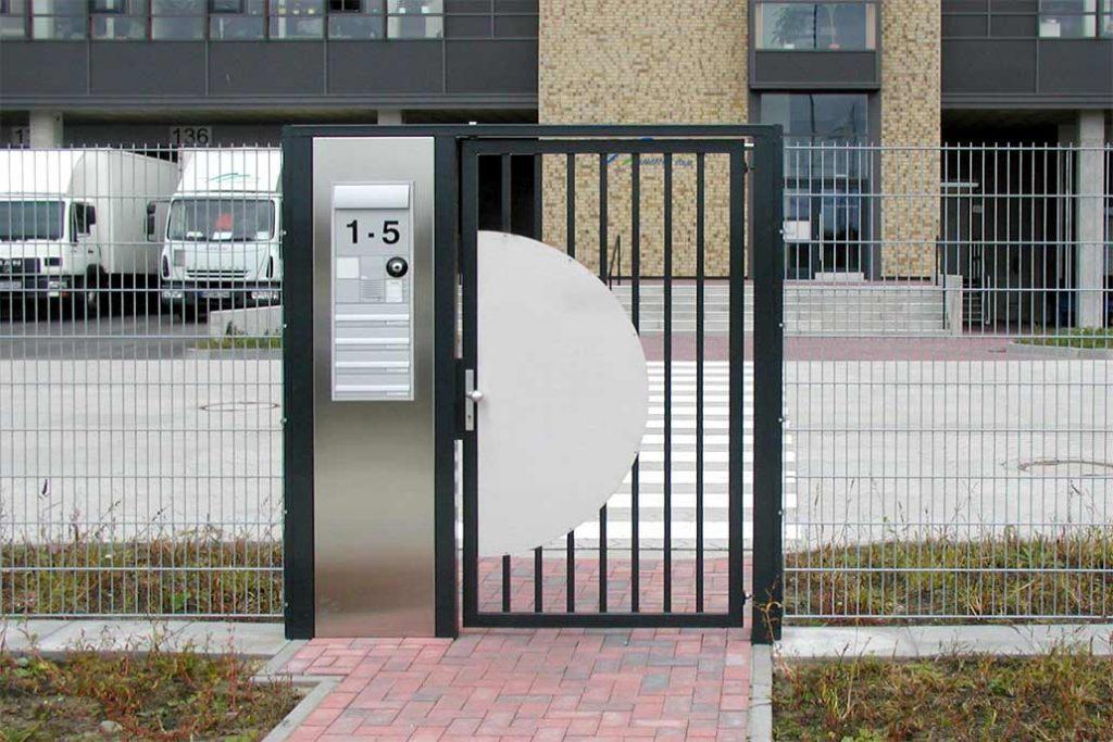 Zwei Meter hohe Personentür an einem Gewerbeobjekt. In einem Element links daneben sind Briefkästen, Klingeln mit Gegensprechanlage und Vidoeüberwachung integriert.