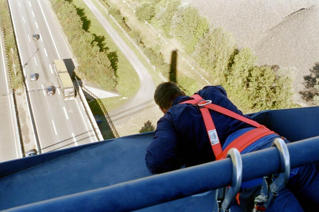 Ein Stahlbauer von Gawron bei Arbeiten an einer Autobahnbrücke im Hafen von Hamburg, gut gesichert mit Blick nach unten auf die Autobahn.