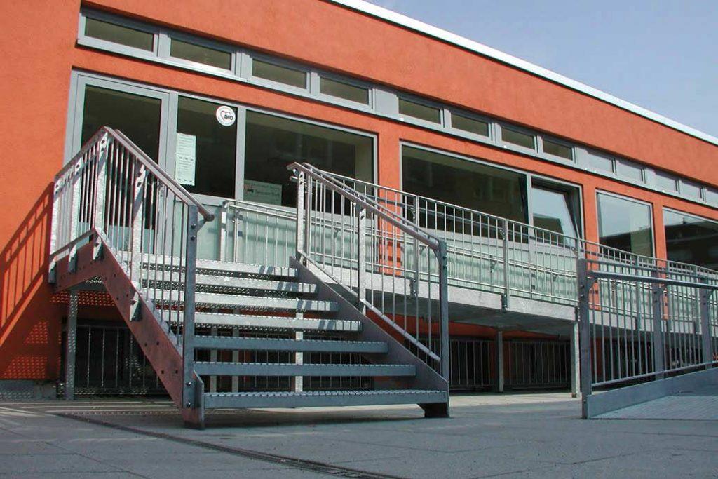 Stahltreppe und Rampe mit Geländer  an einem roten Gebäude.