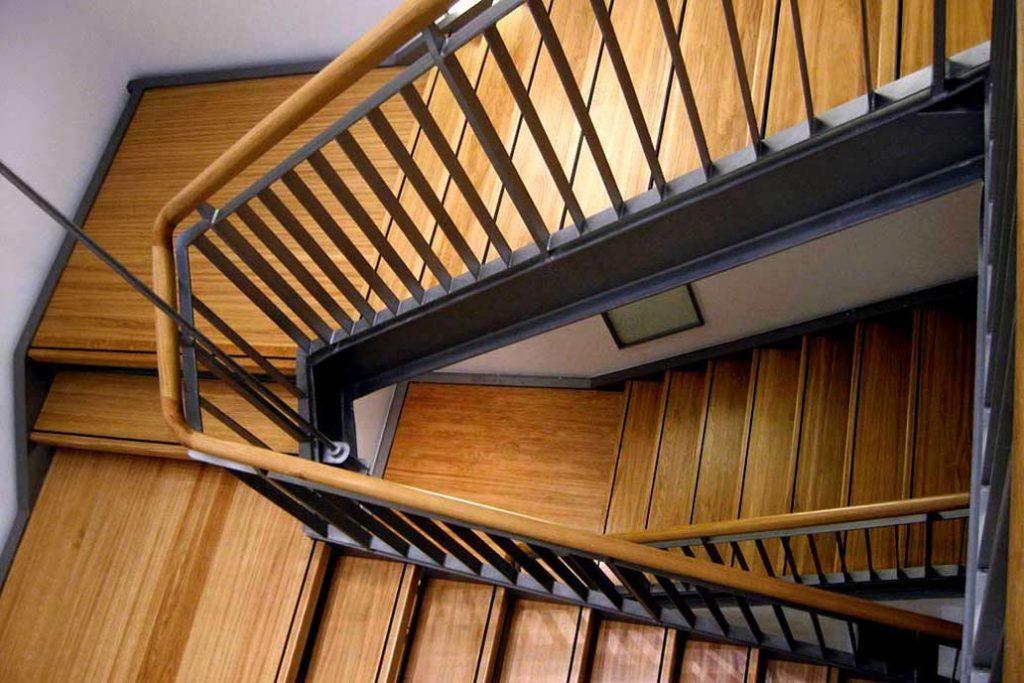 Blick in ein Treppenhaus mit einer Stahltreppe mit Holztrittstufen und Holzhandlauf.