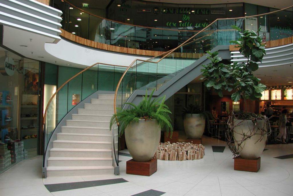 Stahltreppe mit einem Glasgeländer und Holzhandlauf.