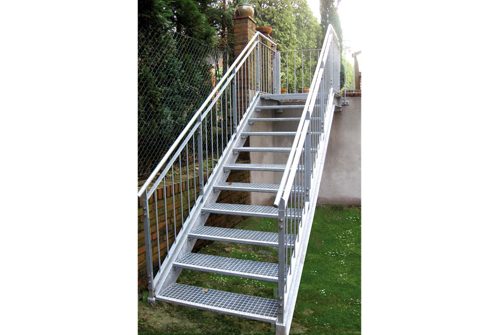 Eine Stahltreppe führt in einen Gartenbereich herunter.