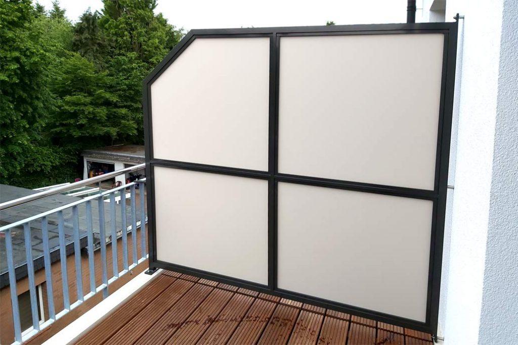 Sichtschutzwand auf einem Balkon aus metall mit einer Füllung aus mattem Glas.