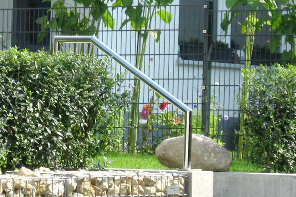 Ein Handlauf aus Edelstahl neben Beton Stufen.